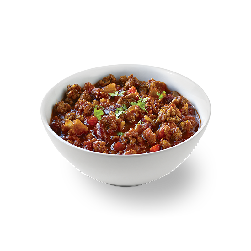 BEYOND BEEF® CRUMBLES in bowl of chili with spoon and corn bread on side